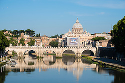 View of Ponte St Angelo across Tiber River and St Peters Basilica Vatican city Rome Italy