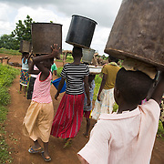 A group of girls carry containers on their head as they head out to fetch water after coming home from school in the village of Ying, in the Savelugu-Nanton district, northern Ghana on Monday June 4, 2007..
