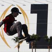 A boy leaps from a tower into an air bag and is momentarily suspended in front of the 2017 log during the championship tailgate party outside Raymond James Stadium in Tampa Monday, January 9, 2017. Staff Photo/Gary Cosby Jr.
