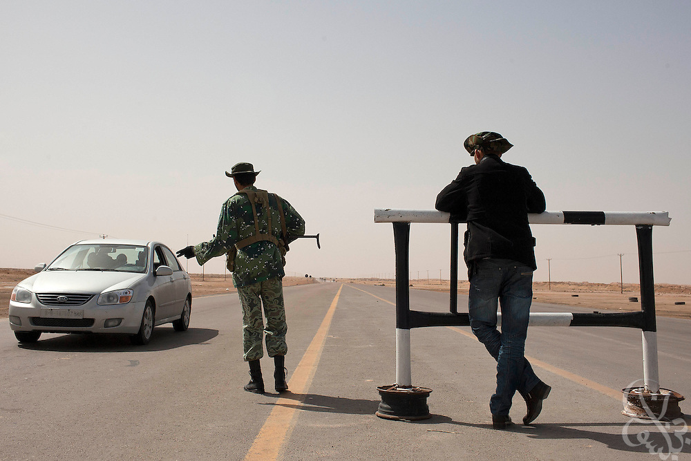 Libyan opposition fighters check passing cars March 1, 2011 at an opposition checkpoint and anti-aircraft position at the entrance of the eastern Libyan city of Ajdabiya. Opposition forces are reported to have repelled Pro-Qaddafi attempts to take back at least three cities around Tripoli today. .Slug: Libya.Credit: Scott Nelson for the New York Times