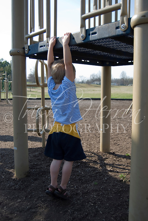 A small boy enjoys playing on the playscape at the park.