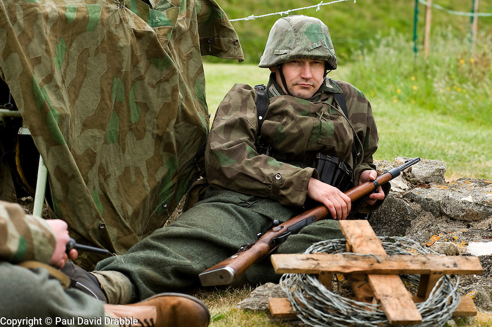 """A reenactor from the Northern World War Two Association portraying a member of the 21st Panzer Division on one of the living history displays at Scarborough Castle. he is wearing a splinter pattern camouflage smock and helmet cover and holding a Mauser Bolt action K98 Rifle. To the left is a splinter pattern camouflage zeltbahn or """"Shelter Quarter""""  Saturday 29th May 2010 .Images © Paul David Drabble."""