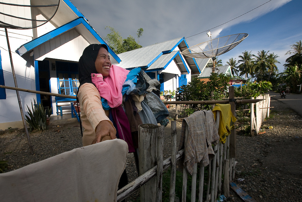 Kuala Trang Village near Meulaboh - Aceh, Indonesia  Nov. 2008. (Heifer Participant) Purwatik gathers her laundry in front of her new built house. The entire village was detroyed during the Tsunami