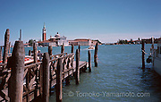 San Giorgio Maggiore seen across the San Marco Basin from the pier with wood mooring posts.  The blue sky was clear except for low-lying clouds. Photo of Venice, Italy by Tomoko Yamamoto. Original on 35mm slide film. Foto des Becken von S. Marco mit S. Giorgio Maggiore, Venedig, Italien. Venezia, Italia