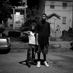 "Hassan (left) works as a brick layer, but sells pirated and pornographic movies on the street to make ends meet for his two daughters. He stopped to take this photograph with a passing basketball player (right) whose height caught his attention. When asked what he thought about the neighborhood the player, who is new to Anacostia responded, ""it's not as bad as everybody says."""