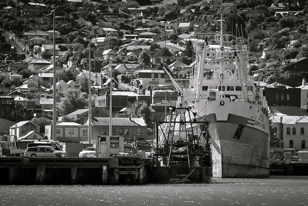 Telephoto shot of a Ukrainian fishing vessel moored at Lyttelton Port of Christchurch alonside smaller fishing boat, with Lyttelton streets and houses beyond
