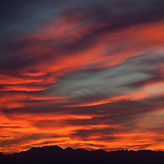 A dramatic, fiery sunset colors the sky above the Olympic Mountains in Washington state. This view was captured from West Seattle, Washington. Several mountains in the range are visible, including Mount Constitution.