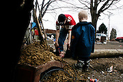 Andrew Goins playfully puts his cousin Dylan in the nearly 5 foot deep hole that was dug for a power pole to be installed for their grandmother Leetha's new trailer on March 8, 2006 in Chauncey, Ohio.