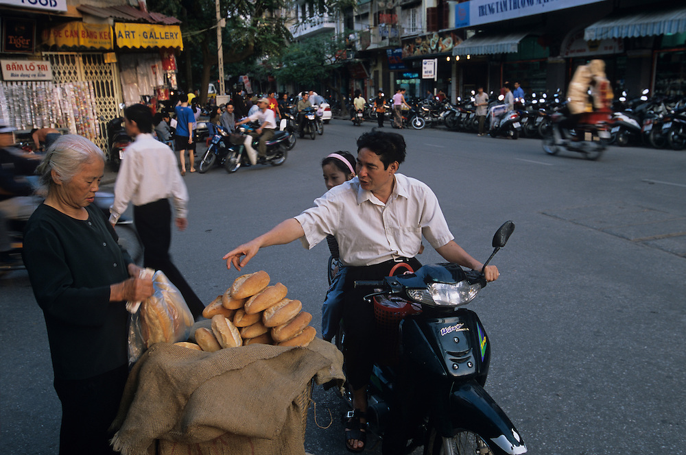 Asia, Vietnam, Hanoi, Man buys freshly baked baguettes from motorcycle along Hoan Kiem Lake in city's Old Quarter