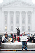 UW-Madison sophomore Adam Cooper holds a sign in support of labor conditions in Wisconsin at the Capitol's footsteps. Wisconsinites rally to protest Wisconsin Governor Scott Walker's budget repair bill at the Capitol Wednesday, February 16 in Madison, Wis. Kris Ugarriza - Red Wave Pictures