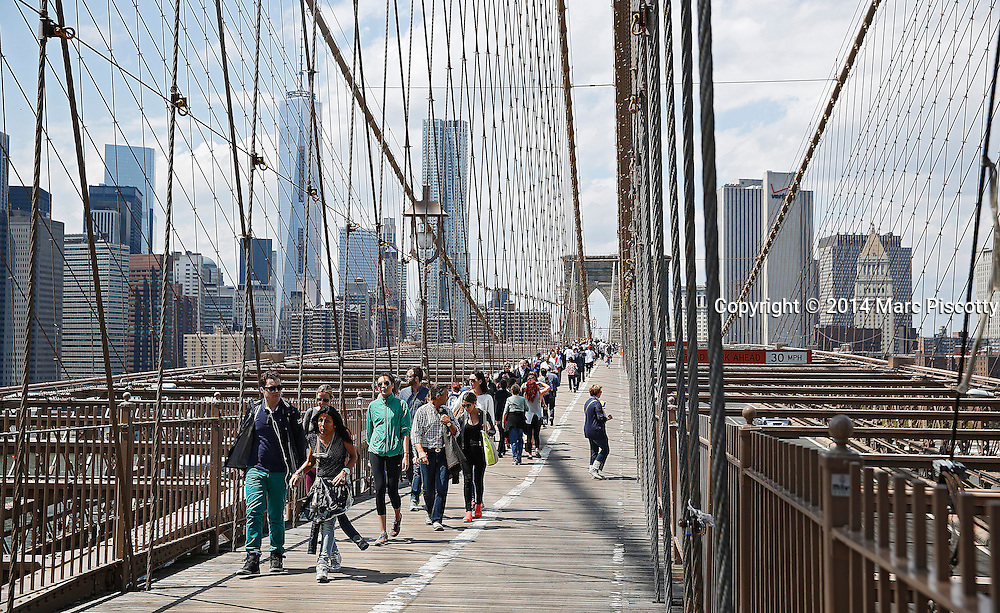 SHOT 5/3/14 11:42:23 AM - Tourists and locals walk across the Brooklyn Bridge in New York City, N.Y. The Brooklyn Bridge is a hybrid cable-stayed/suspension bridge in New York City and is one of the oldest bridges of either type in the United States. Completed in 1883, it connects the boroughs of Manhattan and Brooklyn by spanning the East River. It has a main span of 1,595.5 feet (486.3 m), and was the first steel-wire suspension bridge constructed. It was originally referred to as the New York and Brooklyn Bridge and as the East River Bridge. New York is the most populous city in the United States and the center of one of the most populous urban agglomerations in the world—the New York metropolitan area. The city is referred to as New York City or the City of New York to distinguish it from the State of New York, of which it is a part. A global power city, New York exerts a significant impact upon commerce, finance, media, art, fashion, research, technology, education, and entertainment. New York City has often been described as the cultural and financial capital of the world. (Photo by Marc Piscotty / © 2014)