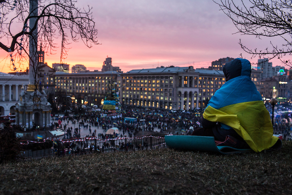 KIEV, UKRAINE - DECEMBER 4: A person wrapped in a Ukrainian flag watches the sun set over Independence Square on December 4, 2013 in Kiev, Ukraine. (Photo by Brendan Hoffman/Getty Images)