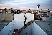 Tijuana Mexico ..photo artist Aldo Guerra on the roof of his apartment ..While working on this long term project 'La Frontera' I want to examine the cultural and humanitarian activities on both sides of a border that keeps the United States and Mexico apart with a wall of steel already 600 miles long. The turf wars of drug cartels, arms trafficking and rampant kidnappings turned cities like Tijuana into some of the most dangerous places on earth. Despite the violence many brave artists, photographers, architects, poets, humanitarians, teachers etc live and work in the shadow of the wall on both sides and have a positive influence on this region; they are the focus of my long term project along the border. (Over time I plan to cover the entire length from the Atlantic to the Pacific, these images were taken in and around Tijuana).© Stefan Falke