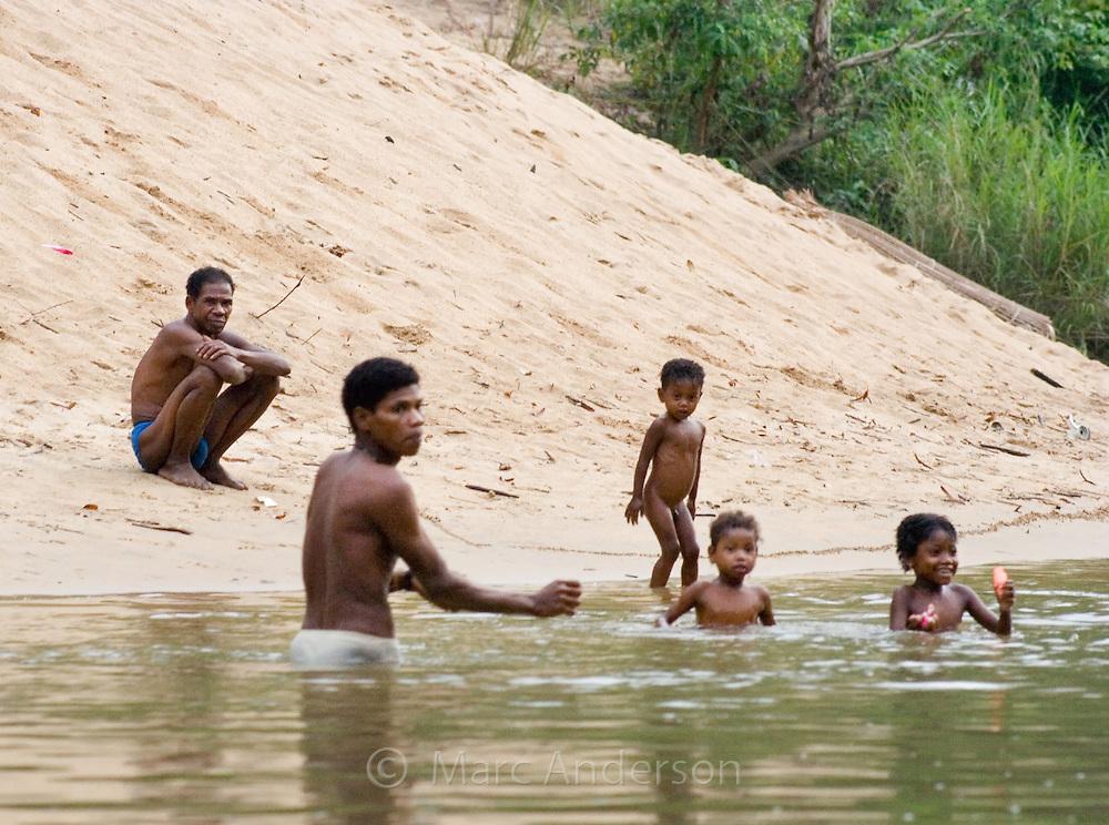 Indigenous Orang Asli people bathing in the Sungai Pahang River, Taman Negara National Park, Malaysia..