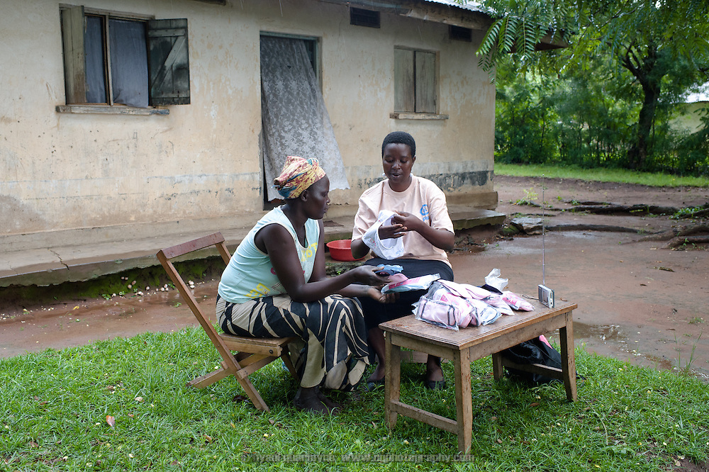 "Lovisa Wankya (right), a teacher and an Afripads dealer, in front of her home near Tororo in Eastern Uganda, explaining how Afripads work to Caroline Adongo on 1 August 2014. Having heard of Afripads and ""Madam Wankya"" on the radio, Caroline was interested in them, but didn't know how to contact Lovisa. She happened to be passing by, and was excited to meet ""Madam Wankya"" and learn about Afripads. She decided to buy two kits, one for herself and one for her daughter. (Afripads are reusable fibre sanitary pads that are having a revolutionary impact on menstrual hygiene management, particularly amongst girls and women who cannot afford expesive disposable pads, and who previously had to use rags, cotton wool or toilet paper.)"