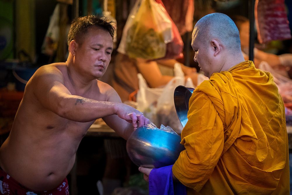 Giving and reciving alms in the Khlong Toei Market, Bangkok, Thailand PHOTO BY LEE CRAKER
