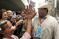 Jason Moore, a Texas delegate with the Republican National Convention from Odessa, high fives demonstrator Medea Benjamin as he talks to reporters and protestors pig snouts, costumes and a Dick Cheney mask rally outside of the Hilton Hotel August 31, 2004 in New York City. Halliburton was hosting a breakfast inside the hotel for the Texas delegates to the RNC.