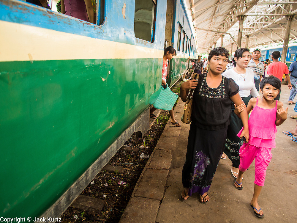 05 JUNE 2014 - YANGON, YANGON REGION, MYANMAR: People get off the Yangon Circular Train in Yangon. The Yangon Circular Train is a commuter train that circles Yangon, Myanmar (Rangoon, Burma). The train is 45 kilometers long, makes 38 stops and takes about three hours to make a loop of the city.     PHOTO BY JACK KURTZ