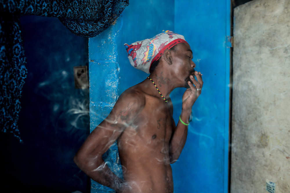 Emmanuel Deus, a musician, smokes marijuana at his home on Thursday, December 18, 2014 in Port-au-Prince, Haiti. Fort National was among the hardest hit areas of Port-au-Prince in the 2010 earthquake, but rebuilding has been slow to non-existent. Residents still mostly lack electricity and running water.