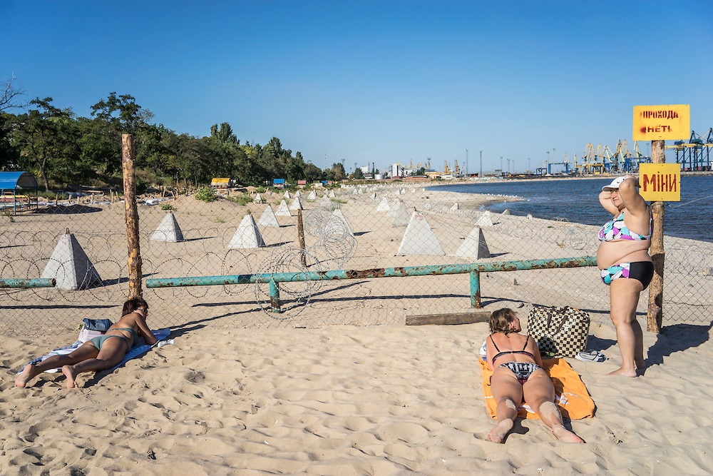 MARIUPOL, UKRAINE - AUGUST 30, 2015: Sunbathers relax on Peschanka Beach, part of which has been fenced off and studded with tank traps and concertina wire to guard against an invasion from sea, in Mariupol, Ukraine. The beach is located on the western side of the city, away from the direction of the front lines. The sign on the fence warns of land mines. CREDIT: Brendan Hoffman for The New York Times