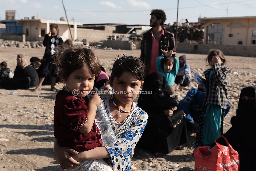 Iraq, Gogjali: Iraqi families, who fled the fight against jihadists of the Islamic State group in the city of Mosul, are seen as they wait to board a truck before heading to camps housing displaced people on November 2, 2016 near Gogjali, which lies on the eastern edge of Mosul. Alessio Romenzi