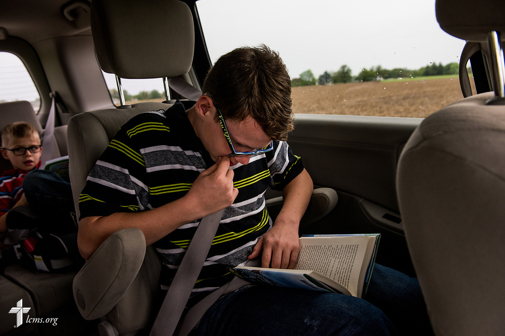 Viktor Fritsche, son of the Rev. Joel Fritsche, career missionary to the Dominican Republic, reads while him and his family drive to a presentation on Wednesday, April 26, 2017, in Staunton, Ill. Along with Viktor are his brothers Andrei (left) and Sergei (not pictured), and Clarion and Joel.  LCMS Communications/Erik M. Lunsford