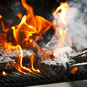 SHOT 7/18/14 6:54:06 PM - Flames lick at ribeye steaks on the grill as chefs prepare dinner for the Sports Executive Leadership Conference at the Broadmoor Hotel's Cheyenne Lodge in Colorado Springs, Co. Activities included a presentation by HawkQuest and a game of horse with NBA Hall of Famer Rick Barry. (Photo by Marc Piscotty / © 2014)