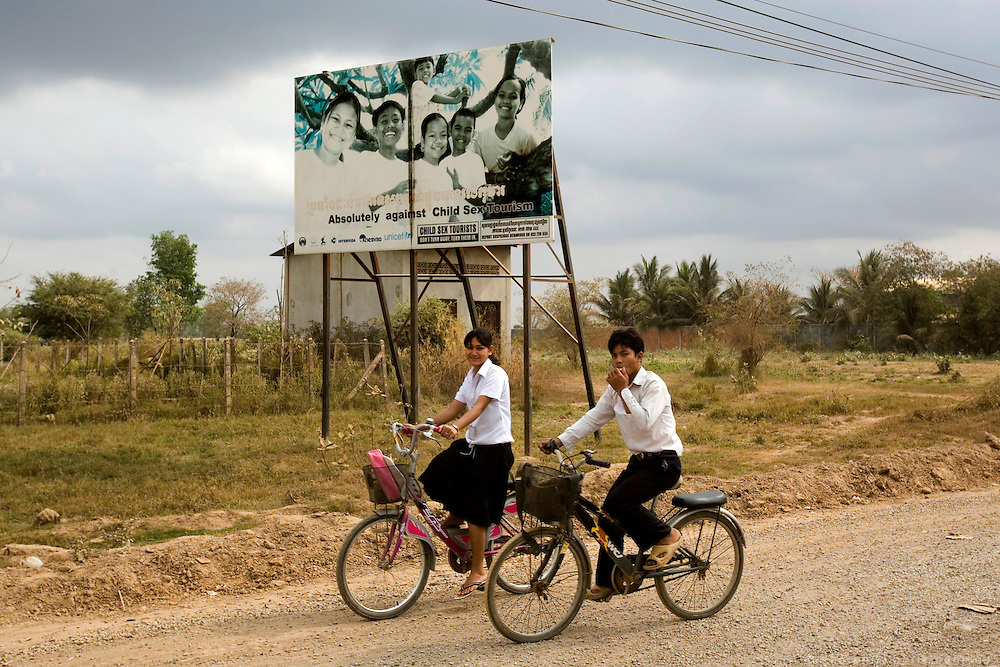 School-kids passing in front of an Anti-Pedophiliac advertisement in the outskirts of Poipek town, near the border with Thailand.