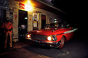 "Red convertible with top down, shiny chrome and red paint on tires at dusk in Puerto Rico parked at old store front with lights on. A ""colmado"" or ""bodega"" Pabon in La Parguera on the southern coast of Puerto Rico."