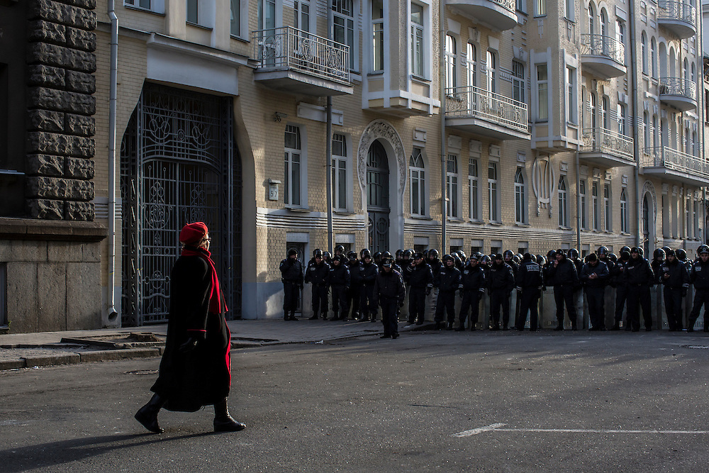 KIEV, UKRAINE - DECEMBER 4: A woman walks near riot police guarding the Presidential Administration building on December 4, 2013 in Kiev, Ukraine. Thousands of people have been protesting against the government since a decision by Ukrainian president Viktor Yanukovych to suspend a trade and partnership agreement with the European Union in favor of incentives from Russia. (Photo by Brendan Hoffman/Getty Images) *** Local Caption ***