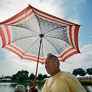SHOT 7/29/2007 - Volunteer Ted Zin of Littleton, Co. tries to shade himself from the sun while watching the 2007 Colorado Dragon Boat Festival from a dock on Sloan's Lake in Denver, Co. Zin said it was the first time he'd been to the races and was enjoying watching while volunteering. The sport of Dragon boat racing is over 2000 years old and features teams of 18 paddlers - nine men and nine women plus someone to steer the boat - all rowing in sync to the beat of a drum and racing to a flag 200 meters away on Sloan's Lake in Denver, Co. Founded in 2001 to celebrate Denver?s rich Asian Pacific American culture, the Colorado Dragon Boat Festival has become the region?s fastest growing and most acclaimed new festival. Festival-goers get to explore the Asian culture through demonstrations, crafts, shopping, eating, and the growing sport of dragon boat racing. .(Photo by Marc Piscotty / © 2007)