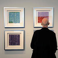 A visitor to an exhibition of prints by artist Lou Stovall pauses to view four variations.