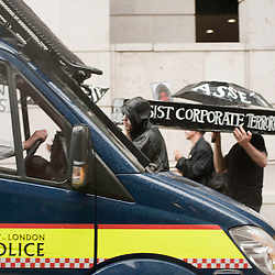 London, UK - 15 June 2012: protesters holding a coffin walking by a police van during the Carnival of Dirt. More than 30 activist groups from London and around the world have come together to highlight the illicit deeds of mining and extraction companies.