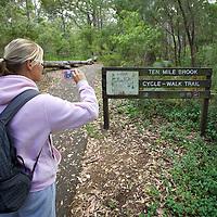 walkway, grass, leaves, bag, pink jacket, women, camera, blonde hair, jogging pants, trees, nature