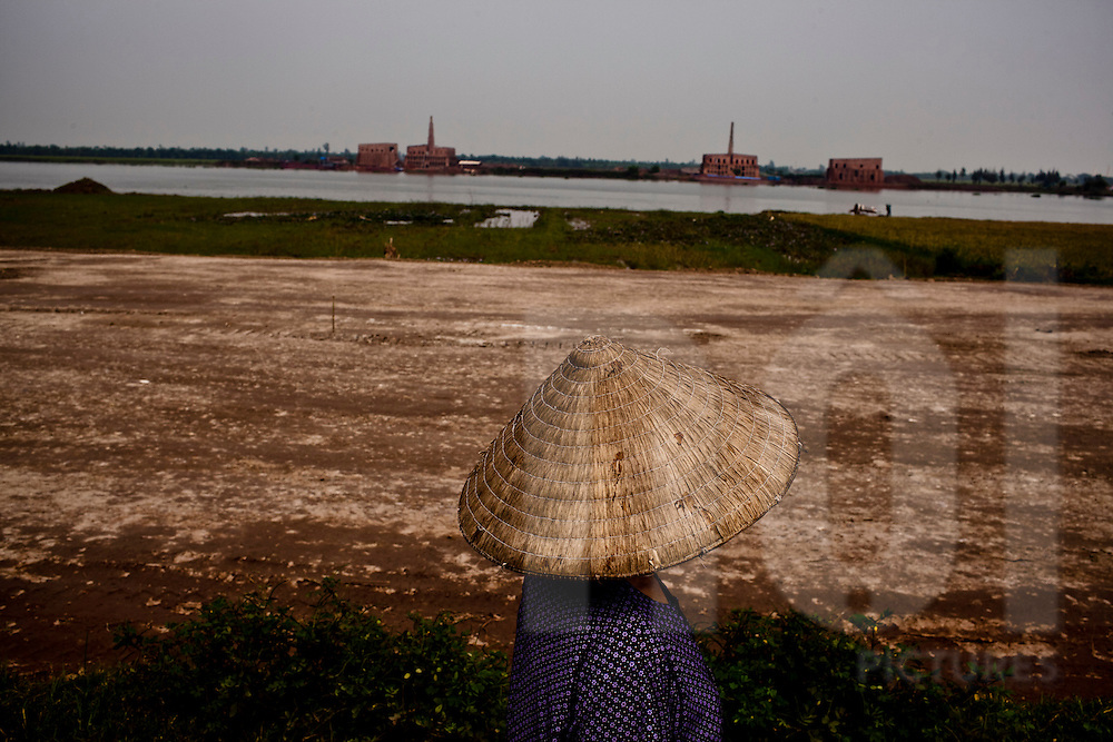An anonymous vietnamese woman walks along the Red River in Ninh Binh Province, Vietnam, Southeast Asia