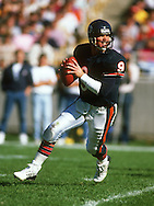 CHICAGO,IL-1988:  NFL quarterback Jim McMahon of the Chicago Bears scrambles with the ball during a game at Soldier Field in Chicago Illinois.  McMahon played for the Chicago Bears from 1982-1988.  (Photo by Ron Vesely)