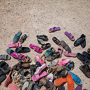 At the entrance to a Mercy Corps child friendly space children remove their shoes before entering the caravan, as is custom to remove ones shoes before entering a room in Arab culture. Azraq camp for Syrian refugees, Jordan, May 2015.