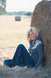 Blonde girl sitting against a round hay bale in a field