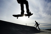 A skateboarder hangs in the air as he skates off the edge, with his group of friends at Jefferson Park Skatepark in the Beacon Hill neighborhood of Seattle. (Markus Yam /The Seattle Times)