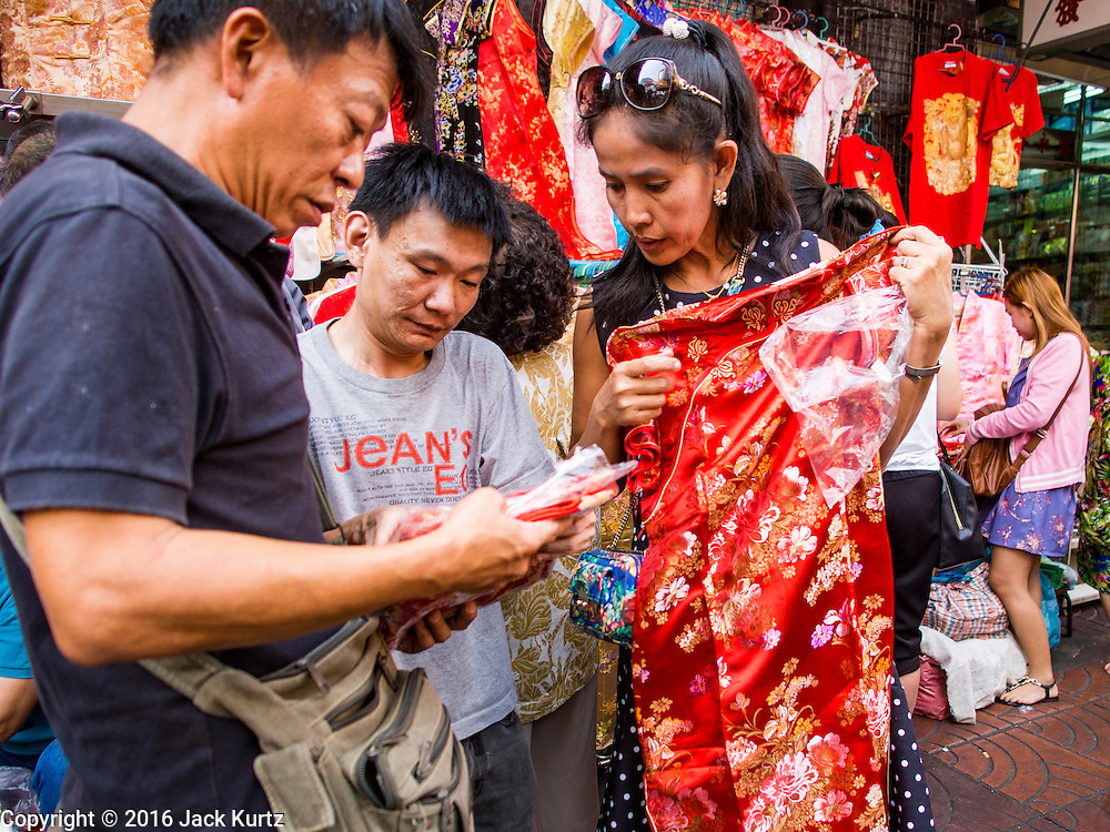 """04 FEBRUARY 2016 - BANGKOK, THAILAND:  Women shop for Chinese New Year dresses in Bangkok's Chinatown district, before the celebration of the Lunar New Year. Chinese New Year, also called Lunar New Year or Tet (in Vietnamese communities) starts Monday February 8. The coming year will be the """"Year of the Monkey."""" Thailand has the largest overseas Chinese population in the world; about 14 percent of Thais are of Chinese ancestry and some Chinese holidays, especially Chinese New Year, are widely celebrated in Thailand.     PHOTO BY JACK KURTZ"""