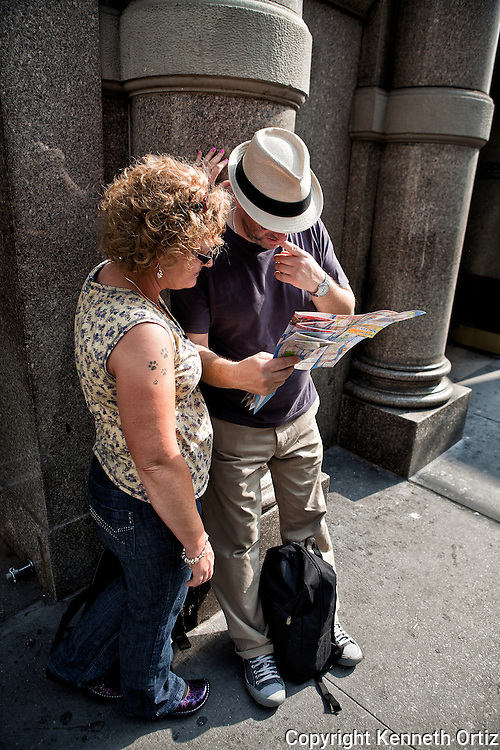 A tourist couple looking for directions in downtown Manhattan, New York City.
