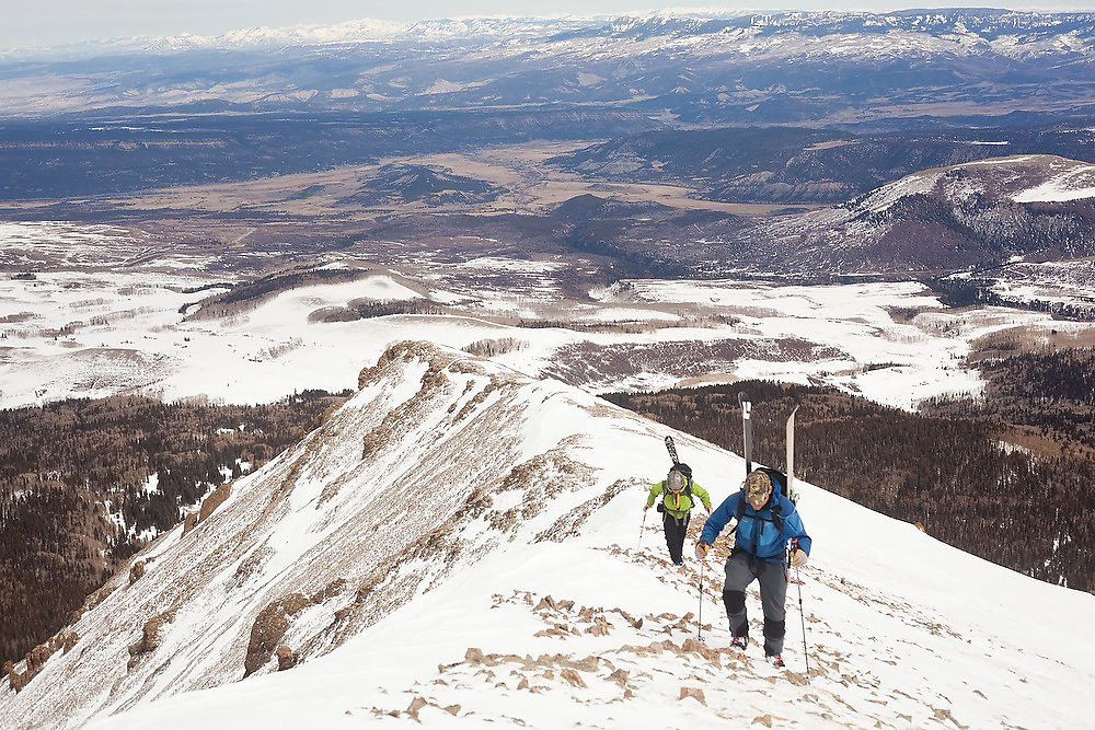Backcountry skiers Sterling Roop and Judd MacRae ascend the summit ridge of Hayden Peak, San Juan Mountains, Colorado.