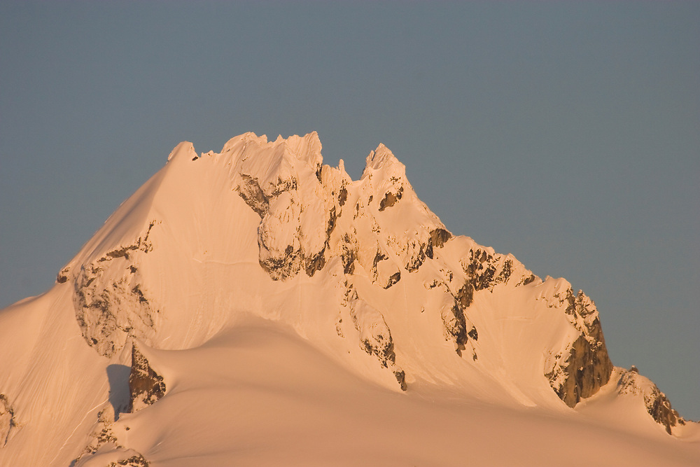 Snow-covered Berg Mt. (4738') lit up with evening alpenglow in Glacier Bay National Park.