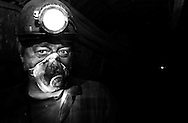 Coalminer, Slawomir Tokarz, takes a moment for a quick break from shoveling coal onto a conveyer belt 650 meters underground at the Piast Coalmine in Bierun, Poland  on April 10, 2002. Most miners wear face masks to avoid getting the fine coal dust into their lungs causing the black lung disease, which is one of the main causes of death for miners..Photo by Jakub Mosur