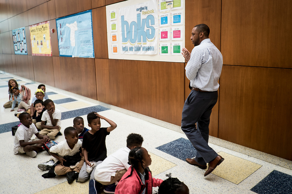 Eric Bethel, principal at Turner Elementary School in Washington, D.C., asks his students math questions as they wait in line to enter the lunchroom on Wednesday, May 4, 2017.