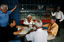 Men play dominoes outside of a bakery setup by the Alexis Vive collective in 23 de Enero barrio.