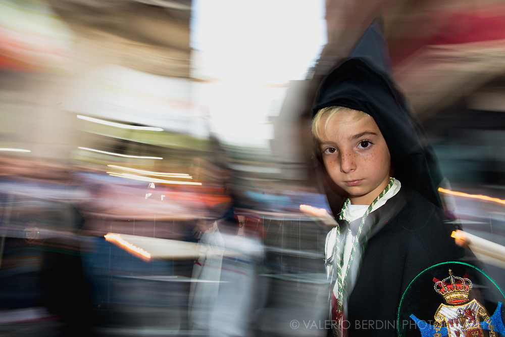 """A child belonging to La Trinidad Brotherhood in the evening of Holy Saturday walk in a central street in Sevilla. Here """"Nazarenos"""", dressed with a black """"capirote"""", the peculiar conical hat, and a white tunic  perform their penance carrying along the procession either long (and heavy) Paschal candles or wooden crosses."""