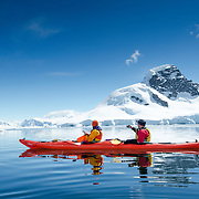 Kayakers glide over the mirror-like surface of calm waters at Cuverville Island on the Antarctic Peninsula on a bright sunny day.