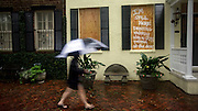 Dana Collins walks past one of her neighbors house in downtown during Hurricane Matthew that has a message to potential looters, Friday, Oct. 7, 2016, in Savannah, Ga. (AP Photo/Stephen B. Morton)