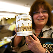 """DENVER - FEBRUARY 26: Rocky Mountain News courts reporter Sue Lindsay lightheartedly displays a mug featuring the Titanic given to her by a friend as she packs up her belongings in the newsroom Thursday. The Rocky Mountain News, one of two of Denver's daily newspapers, announced Thursday February 26, 2009 that tomorrow's edition would be the final one of the newspaper's almost 150 years of publishing. The newspaper had been put up for sale by its owner, E.W. Scripps, but the search for a buyer proved unsuccessful. """"Denver can't support two newspapers any longer,"""" Scripps CEO Rich Boehne told staffers, some of whom cried at the news. """"It's certainly not good news for you, and it's certainly not good news for Denver."""" The Rocky was founded in 1859 by William Byers, one of the most influential figures in Colorado history. Scripps bought the paper in 1926 and immediately began a newspaper war with The Post. That fight ebbed and flowed over the course of the rest of the 20th century, culminating in penny-a-day subscriptions in the late '90s. The closure will cost 228 newsroom employees their jobs..(Photo by Marc Piscotty/ © 2009)"""